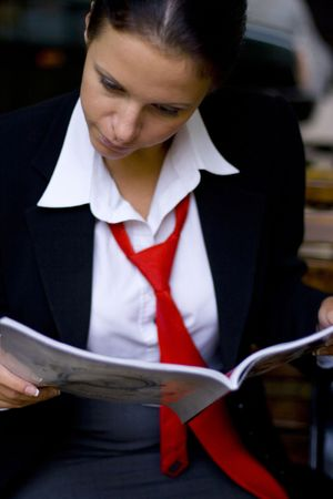 outdoor portrait of attractive young businesswoman reading magazine photo