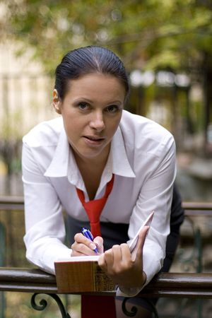 portrait of pretty businesswoman with notebook outside photo