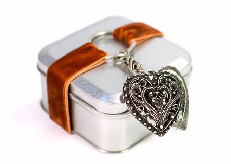 metal gift box with decorative heart on white background photo