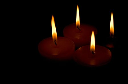 remembrance: four candles on black background Stock Photo