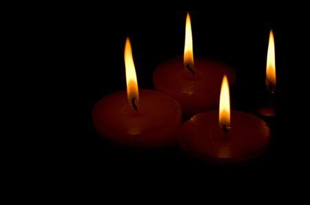 mourn: quattro candele su sfondo nero Archivio Fotografico