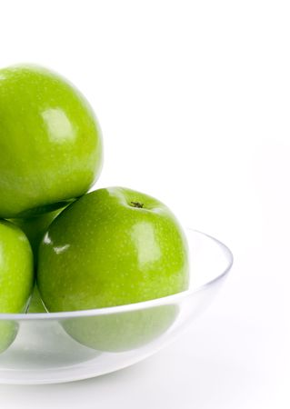 closeup of green apples in glass bowl on white background photo