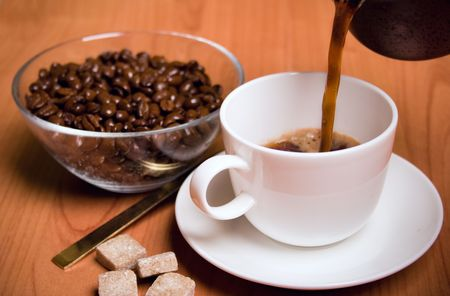 cup of coffee, sugar and beans in glass bowl on wooden table photo