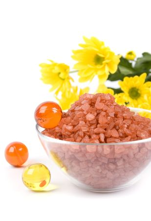 spa pruducts: bath salt, oil balls in a bowl and yellow flowers photo