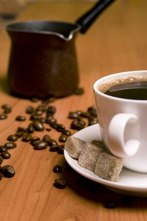 cup of coffee, caffee-maker, sugar and beans on wooden table photo