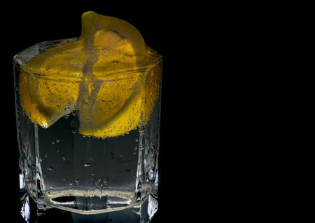 glass with soda water and lemon slices on black background photo