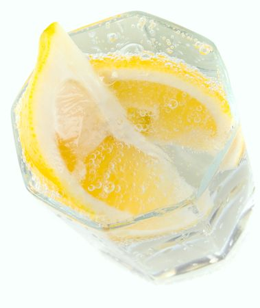 glass with soda water and lemon slices on white background photo