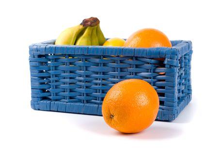 blue basket with fruits on white background photo