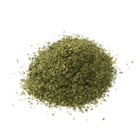dried spice: pile of dried basil spice isolated on white background