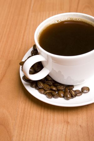 cup of coffee and beans closeup on wooden table photo