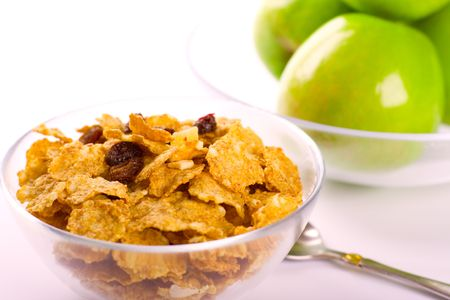 cornflakes and green apples in glass bowls on white background photo