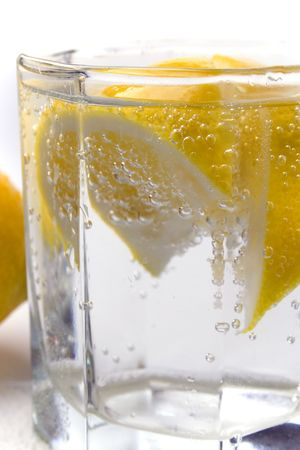 glass with soda water wiht lemon slices closeup photo