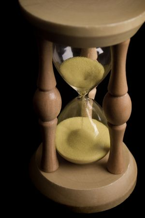 sand clock showing how is time passing on black background photo
