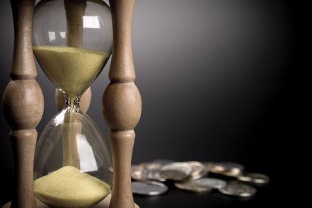 sand clock: orologio di sabbia e le monete su sfondo nero