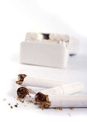 cancerous: broken cigarettes on white backgrounnd
