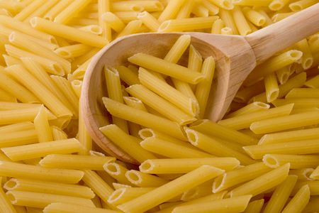raw italian macaroni and wooden spoon Stock Photo - 4576257