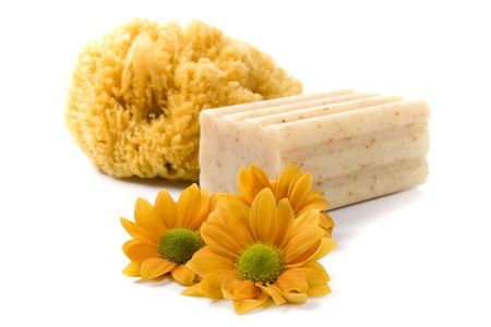 natural sponge, soap and flowers on white background photo