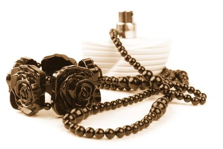 parfume: black necklace, bracelet and parfume bottle on a white background