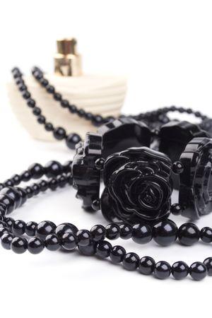 black necklace, bracelet and parfume bottle on a white background photo