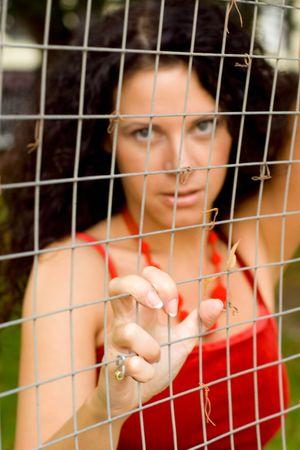 beautiful woman behind a lattice. focus on hand. Stock Photo - 4781251