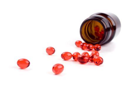glazen fles met rode pillen op witte achtergrond