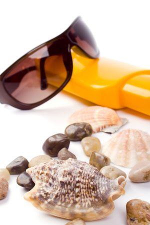 shells, sunglasses and lotion closeup on white background photo