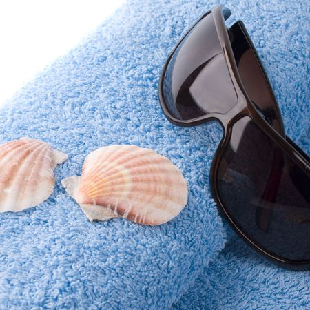 towel, shells, sunglasses closeup on white background photo