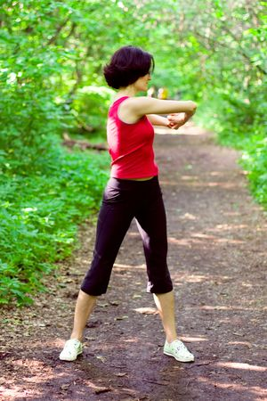 sporty woman working out on a forest path. photo