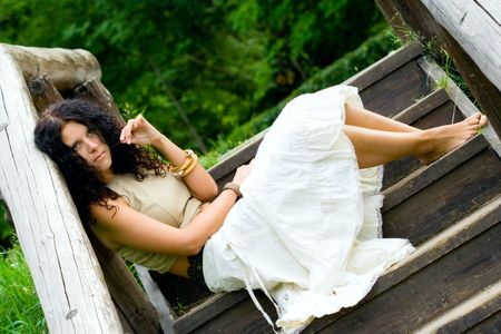 portrait of attractive woman sitting in wooden stairs photo