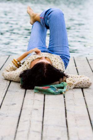 sunset lake: beautiful brunet woman lying near the river Stock Photo