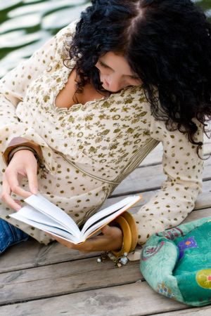 outdoor portrait of a beautiful woman reading a book  photo