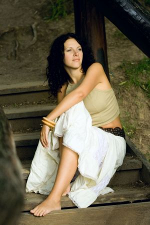 portrait of attractive woman sitting on wooden stairs photo