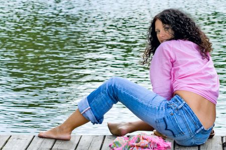beautiful brunet woman sitting near the water photo