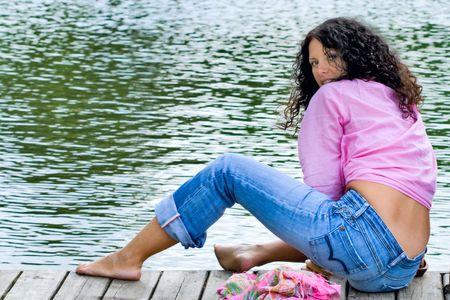 beautiful brunet woman sitting near the water photo