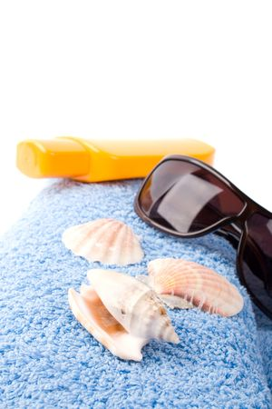 towel, shells, sunglasses and lotion closeup on white background photo