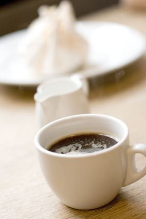 cup of coffee, milk and meringue on wooden table photo