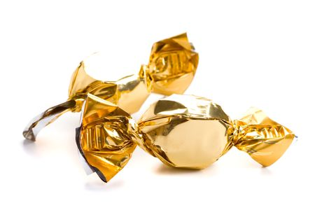 two golden sweets closeup on white background photo