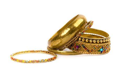 stack of golden bracelets isolated on white background photo