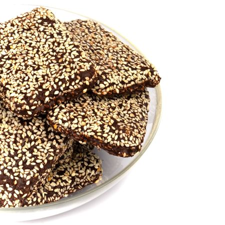 chocolate cookies with sesame seeds in a bowl closeup photo