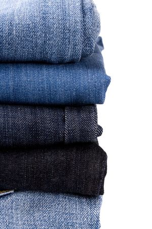 stack of blue jeans closeup on white background photo