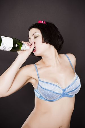 pretty pin-up girl drinking champagne from a bottle on black background photo