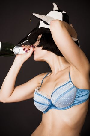 pretty girl drinking champagne from a bottle on black background photo