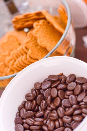 dark chocolate beans in white bowl and cookies closeup  photo