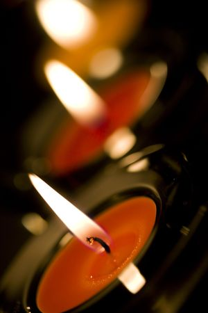three candles flaming in the dark closeup photo