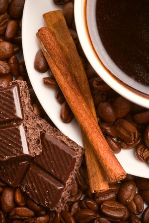 cup of coffee, beans, cinnamon sticks and black chocolate closeup photo