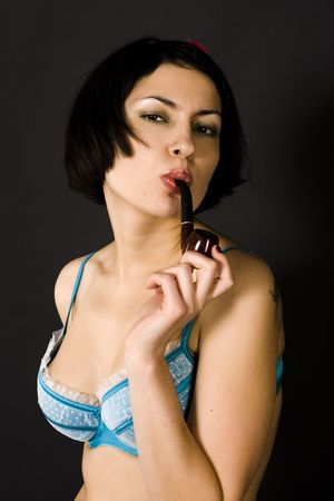 pretty pin-up girl with tabacco-pipe on black background photo