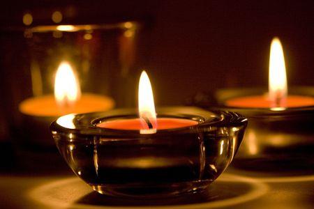 three candles flaming in the dark closeup photo