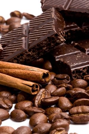 arrangement of chocolate, coffee and cinnamon sticks on white photo