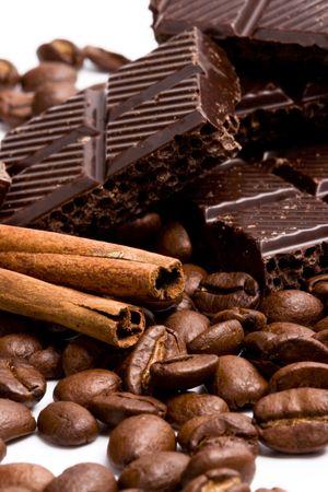 arrangement of chocolate, coffee and cinnamon sticks on white photo