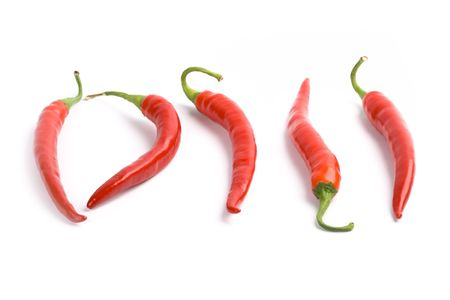 five red chilly peppers isolated on white background photo